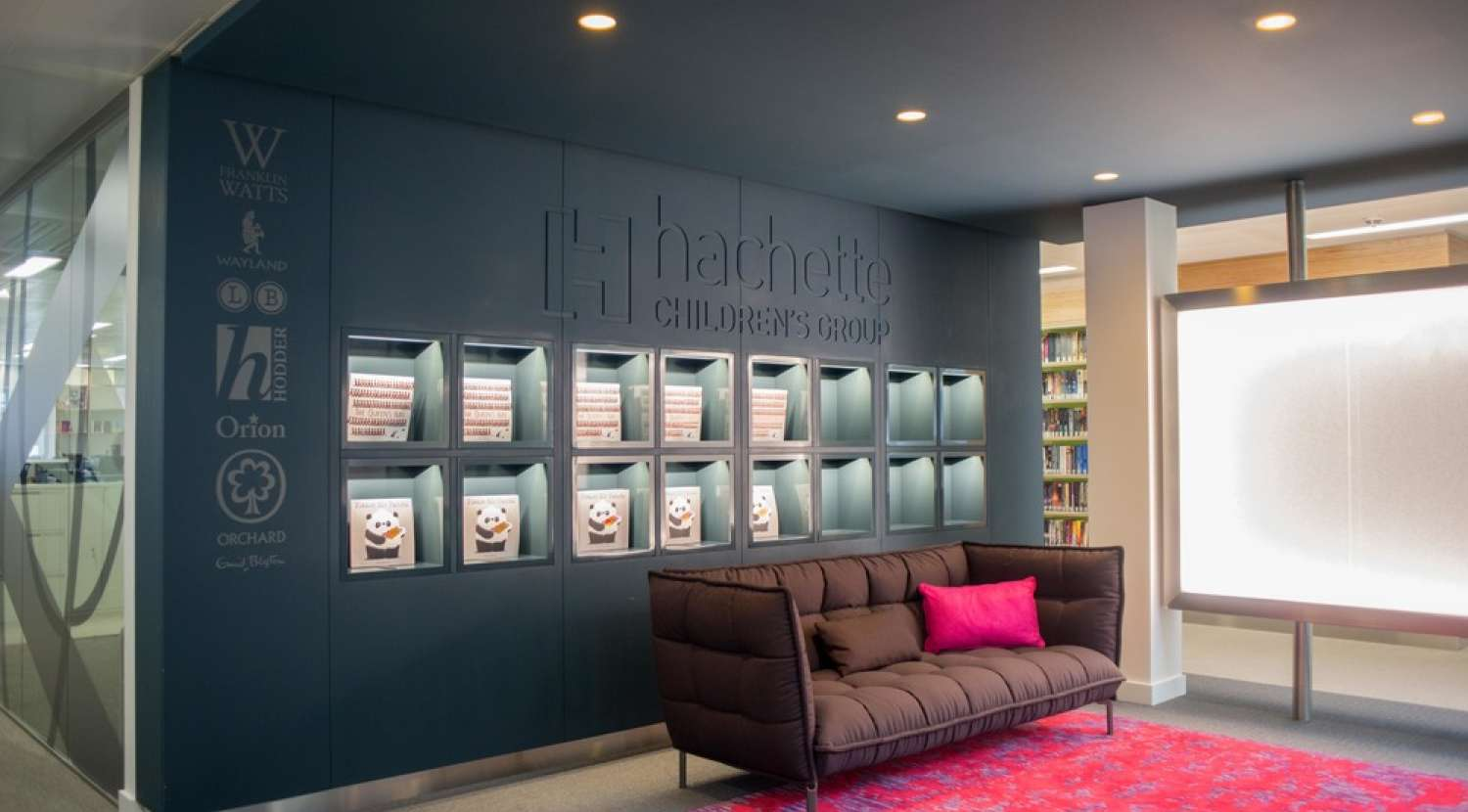 Hacehette reception with branded wall, coloured flooring and a sofa