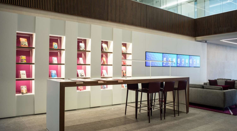 Standing area and illuminated bookshelf in moden london office reception