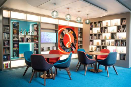 Soft chairs and wooden tables with funky bookshelves in modern office fit out
