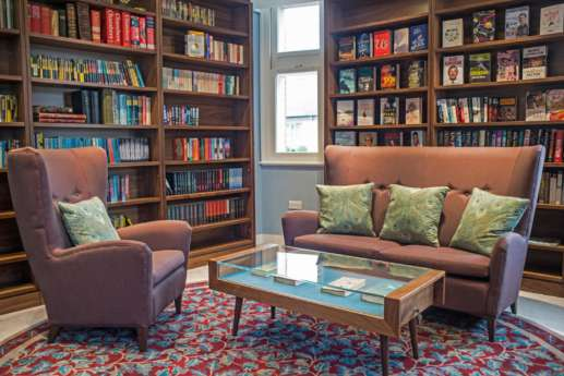 Cosy arm chairs and large wooden bookcases in an informal area in a London office fit out