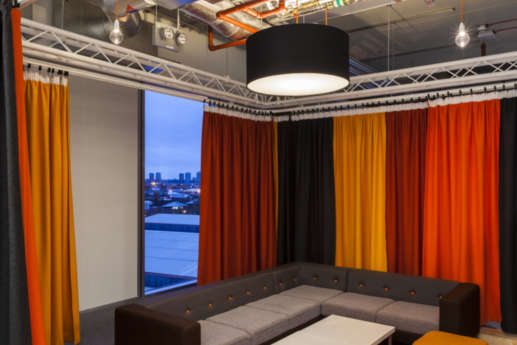 Office with plush chairs and solid drapes overlooking the city