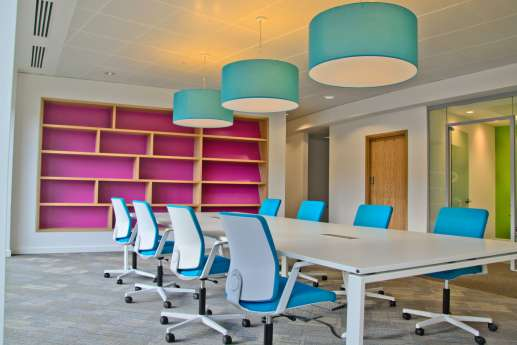 Bright meeting room with blue chairs and pink bookcase