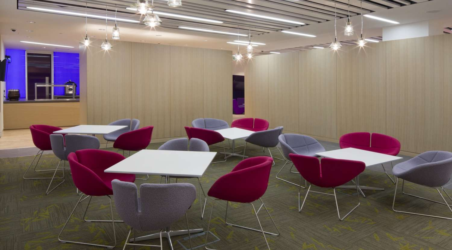 Colourful chairs and wooden paneling in modern london office fit out