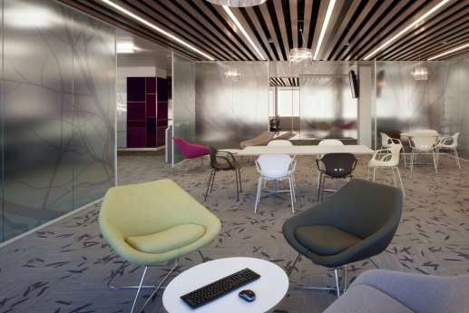 Colourful chairs and glass walls in natural breakout area