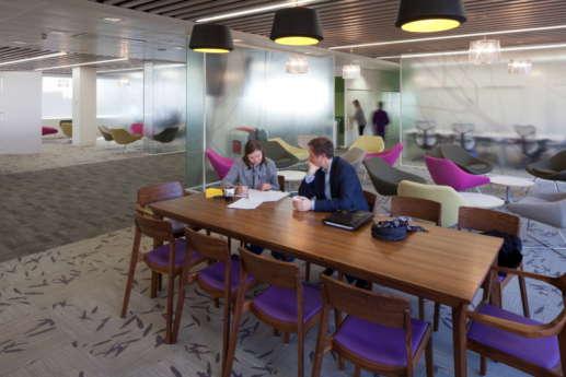 Staff having a meeting at dark oak table in open plan office
