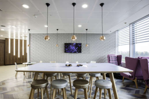 Stylish office breakout area with stools and purple chairs