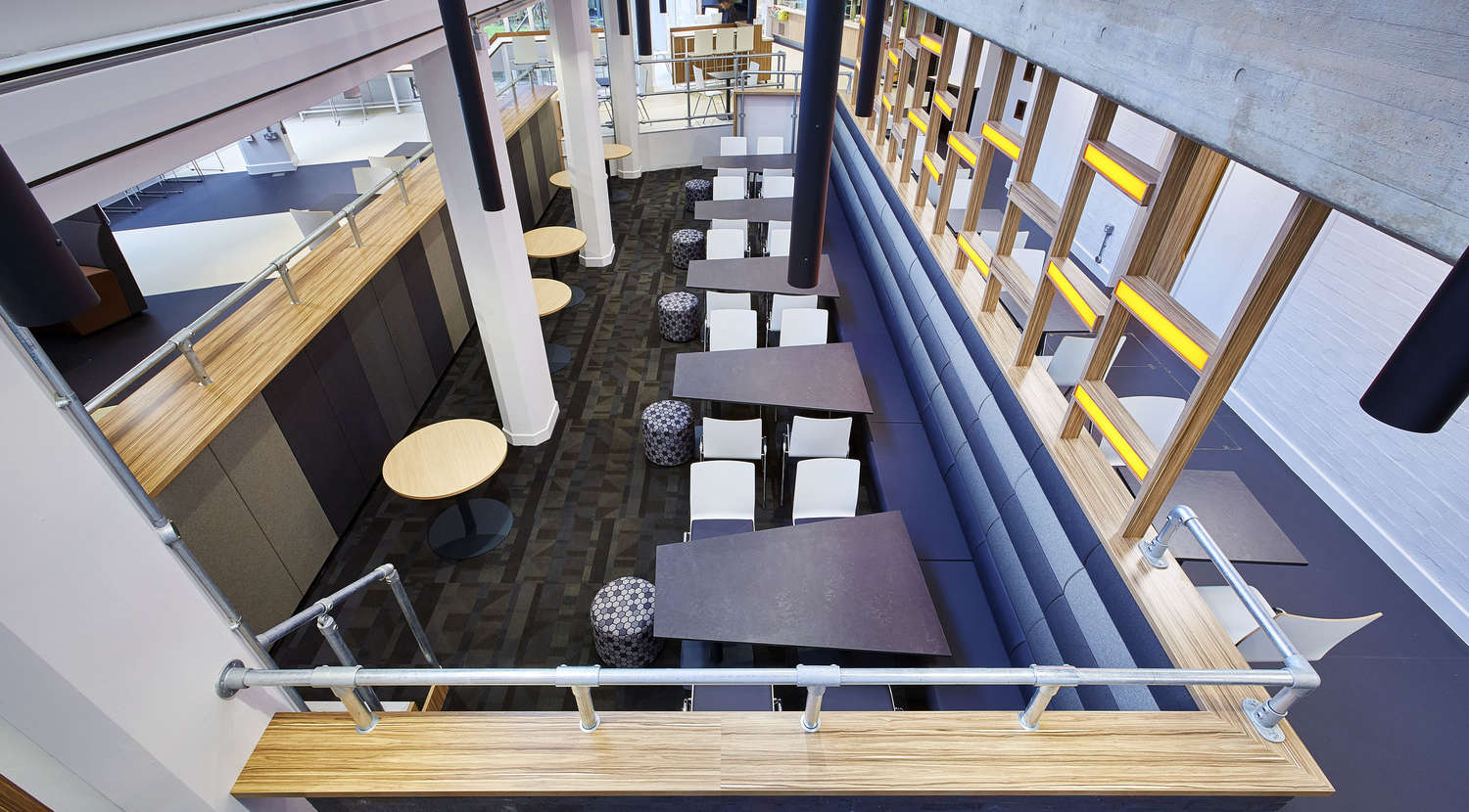 View of tables and bench seating from an office atrium