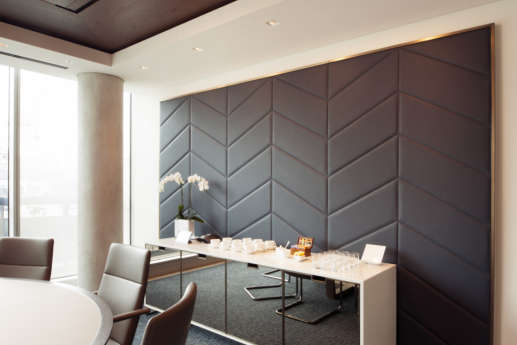 Office meeting room with designer furniture and leather wall feature