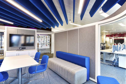 Inside of office meeting pod with sofa, desk and TV