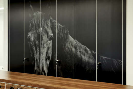 Office with black and white horse print over cabinets