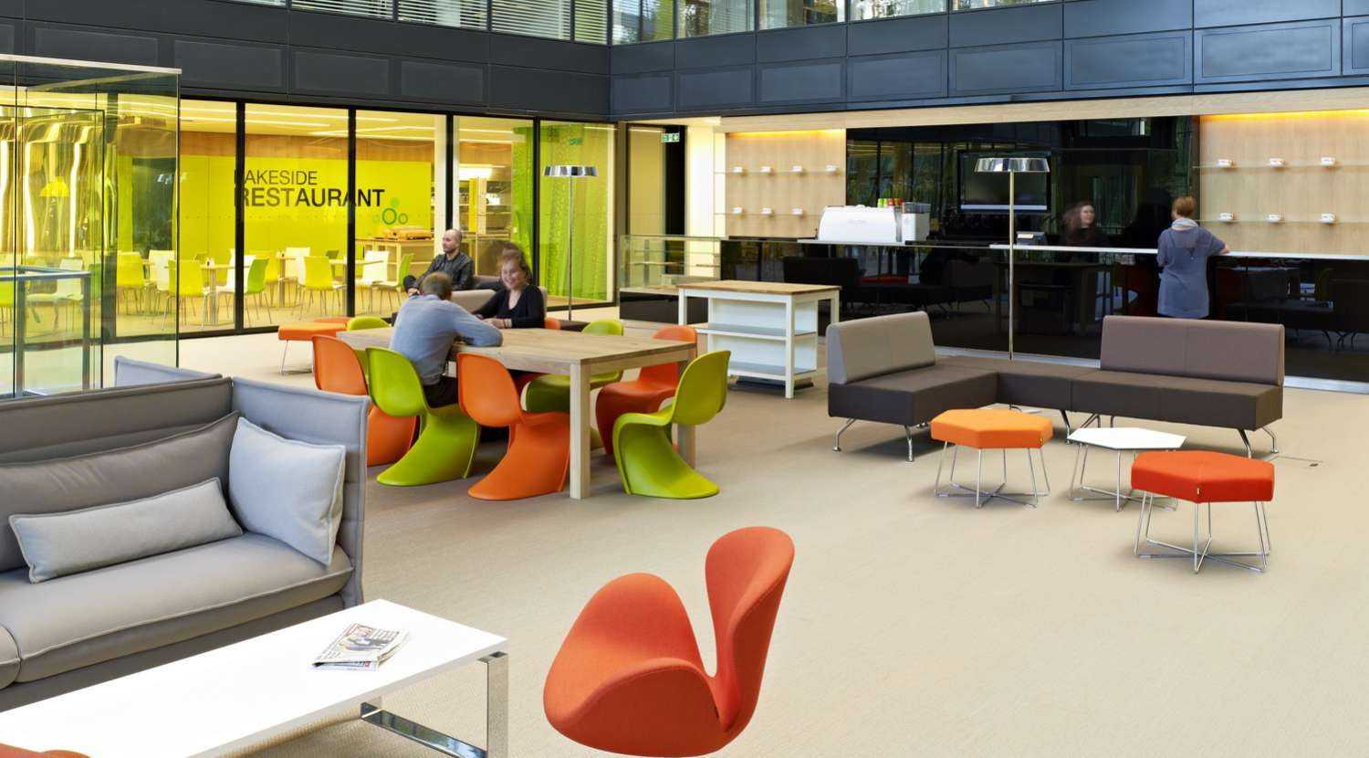 Staff bonding in modern breakout area with colourful chairs