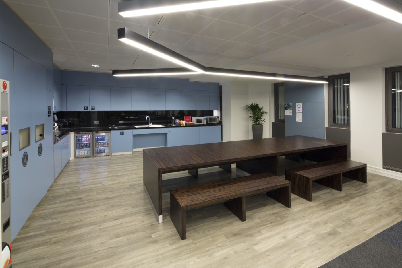 Office kitchen with blue cupboards and communal seating