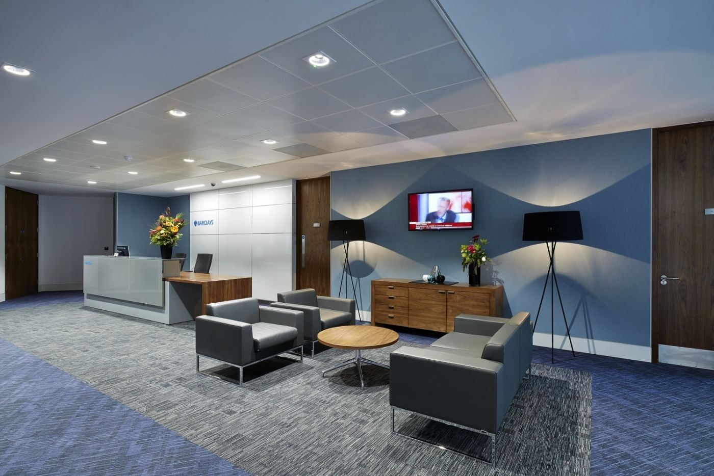 Lamps and sofas in open plan office reception