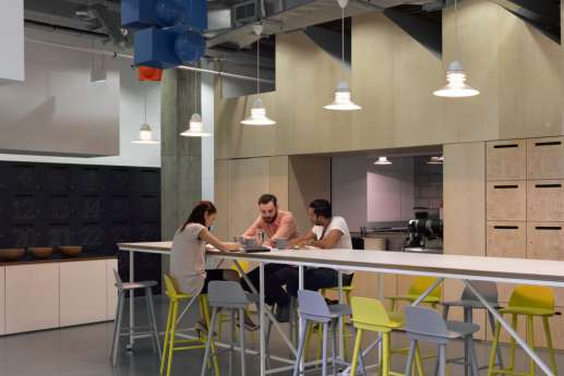 Staff talking in modern warehouse-style office kitchen