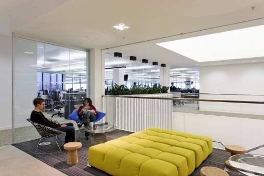 Staff meeting in open plan office breakout area with colourful furniture