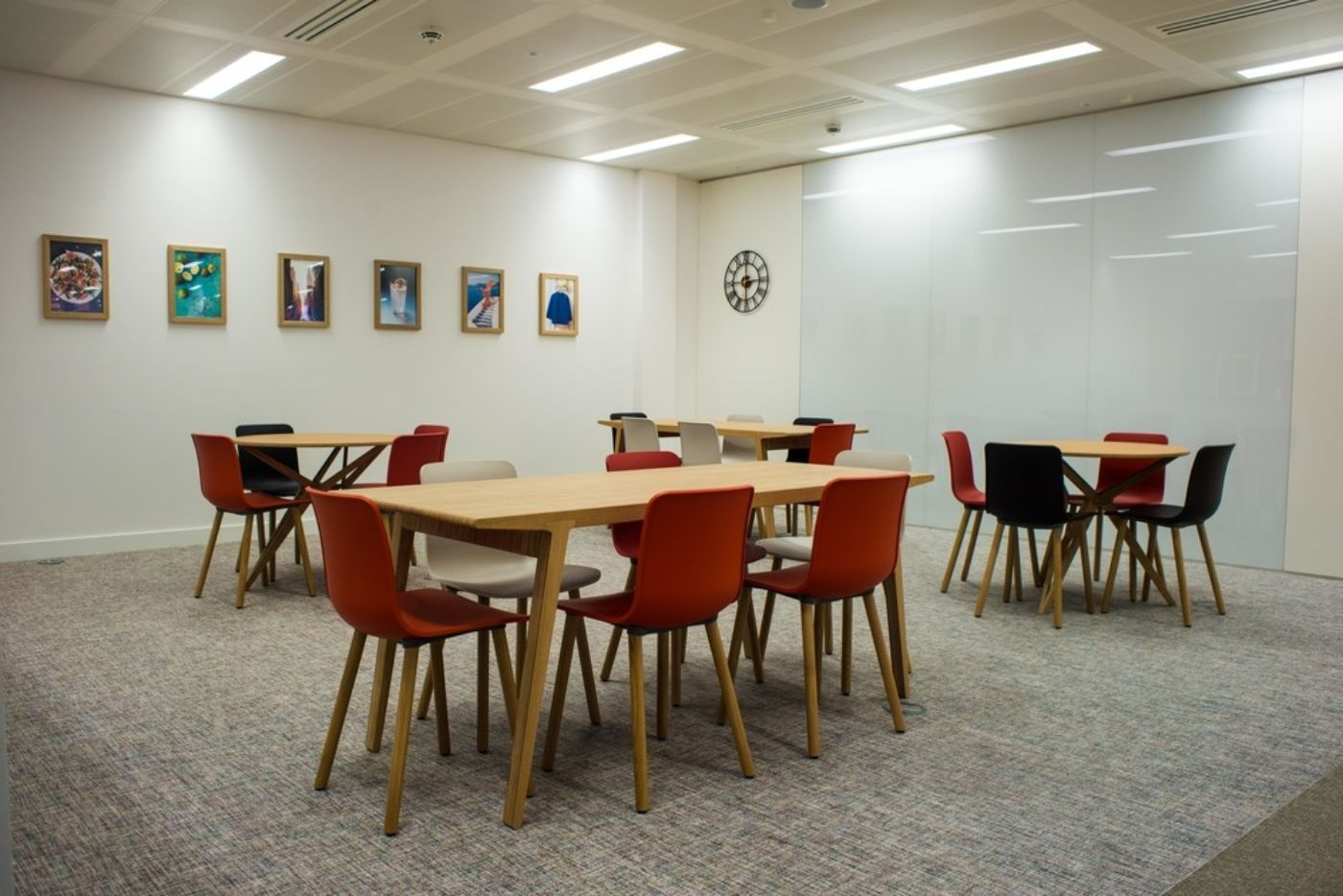 Staff breakout area with wooden tables and coloured chairs in stylish office fit out