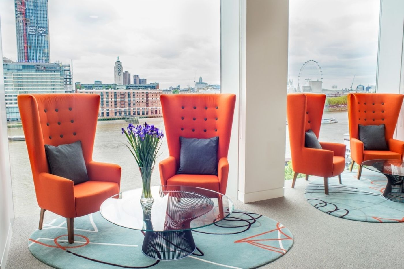 Orange arm chairs looking over the Thames in funky, london office fit out
