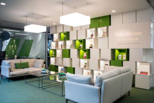 Sofas and green and white bookshelves reflect the brand in this modern fit out
