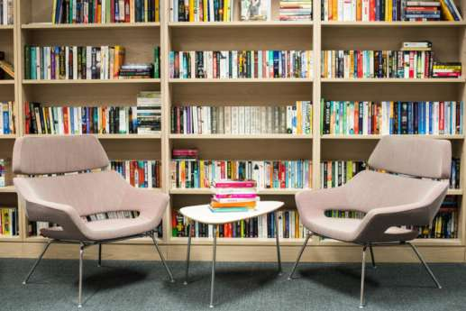 Arm chairs infront of large bookcases in a modern London office