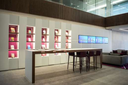 Standing area and illuminated bookshelf in moden london office reception
