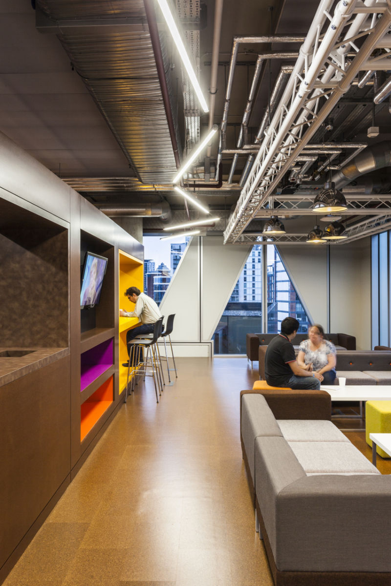 Staff talking in a colourful breakout area in a modern office