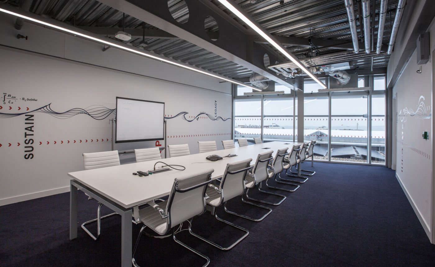 Minimalist meeting room with white chairs in Land Rover's office fit out