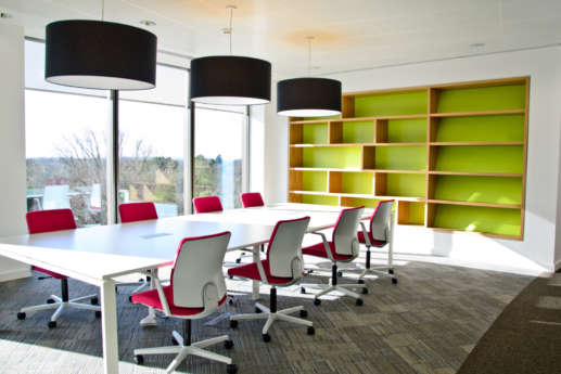Modern meeting space with stylish lamps and bookcase