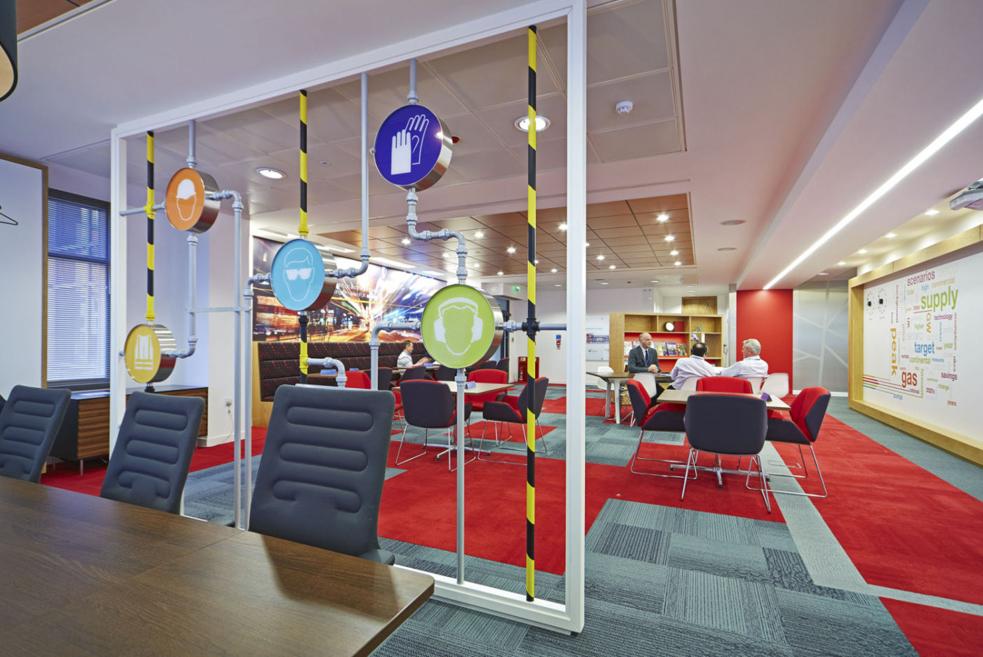 Meeting area divided with exposed pipes and colourful safety graphics