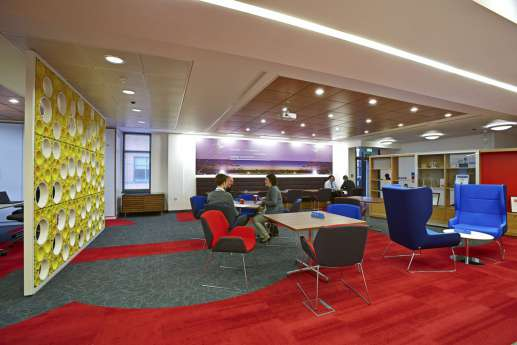 Staff having a coffee in colourful fit out; with red floors, blue chairs and yellow wall