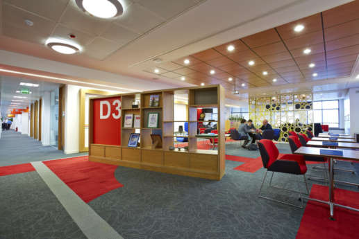 Red themed breakout area, divided by a bookcase showing awards