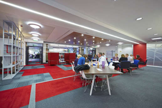 Staff taking in an open plan breakout area with red furniture