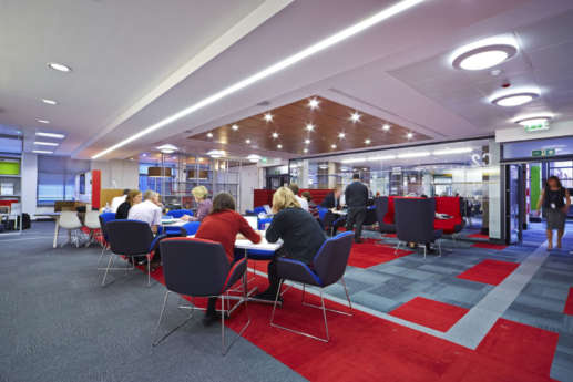 Staff having a meeting in a red themed breakout area in a Warwick office