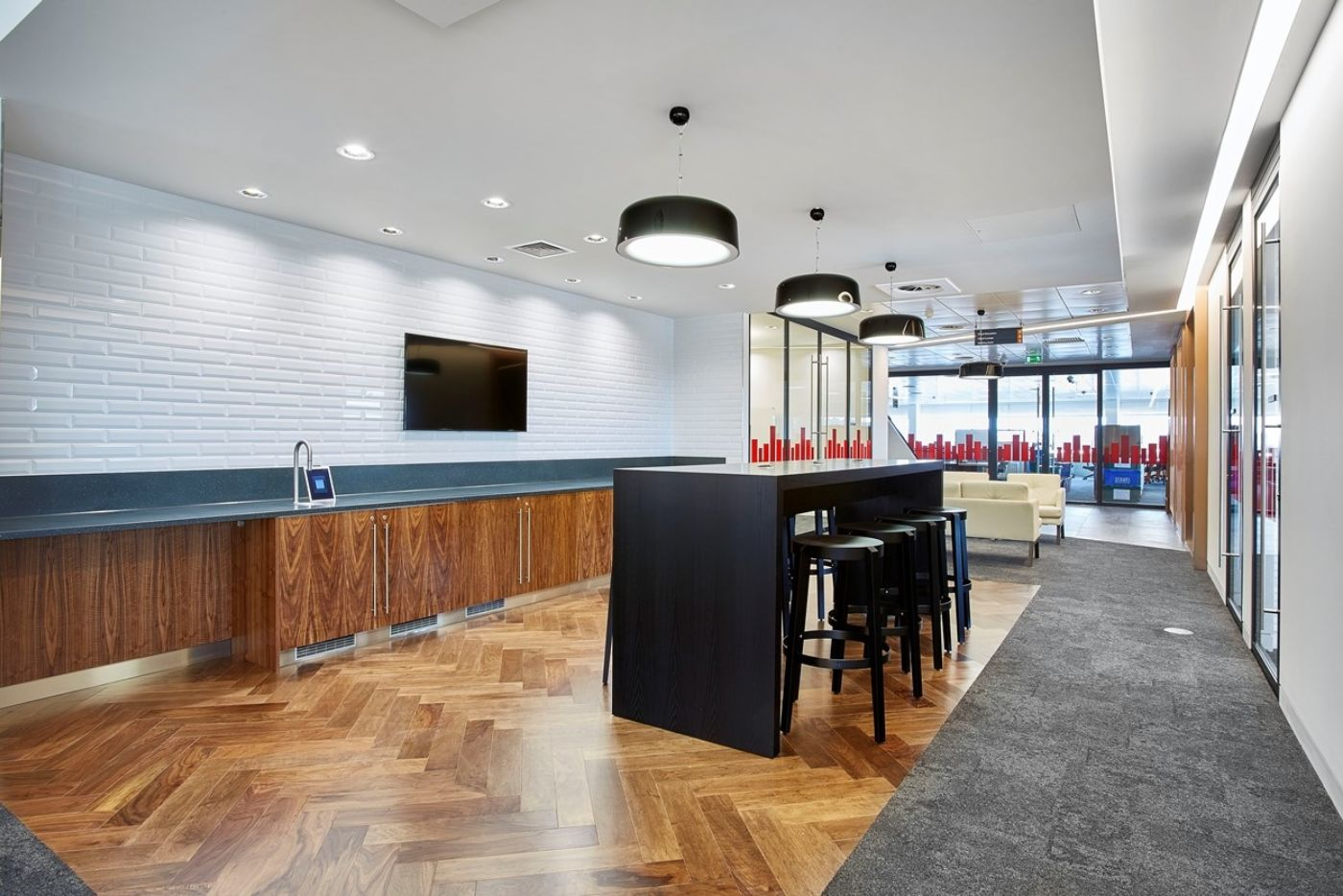 Office kitchen with white tiles and wooden flooring and high-seating