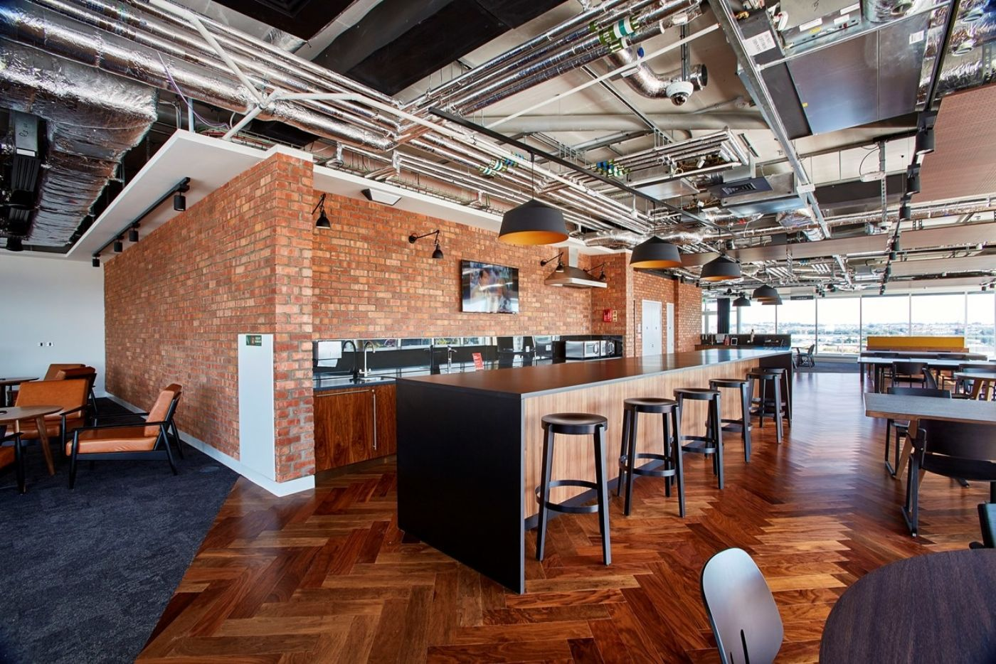 Office kitchen with exposed bricks and wooden flooring in ultra-modern office fit out