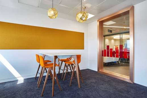 Orange themed meeting room with high chairs and modern furniture