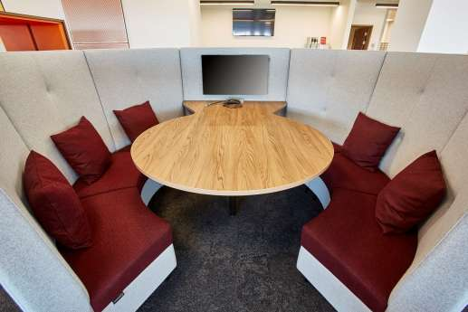 Circular meeting pod with burgundy cushions and wood finishings