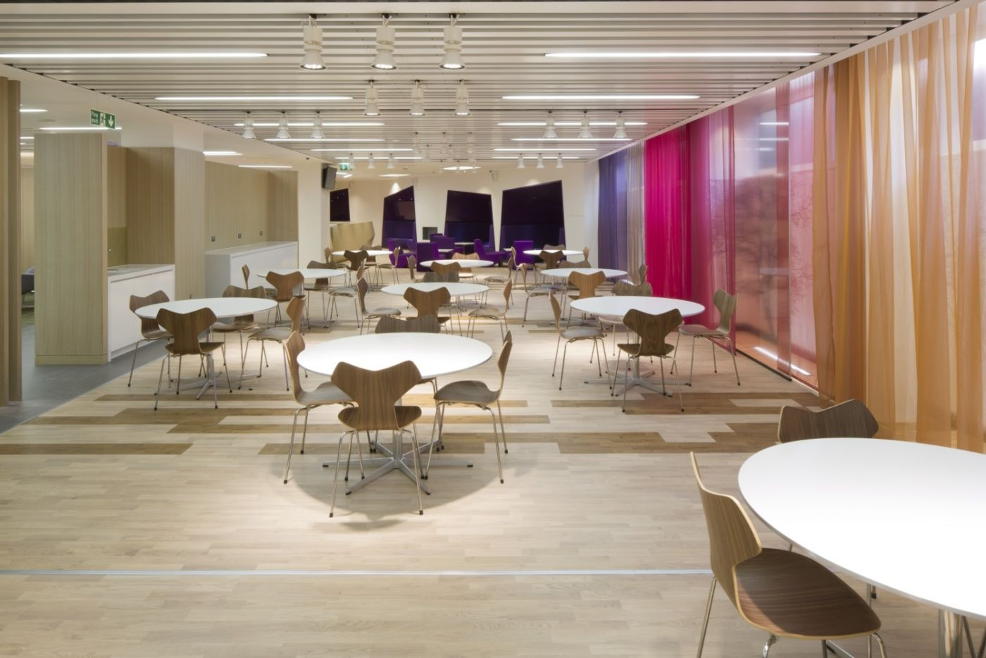 Circular tables in staff breakout area with colourful walls