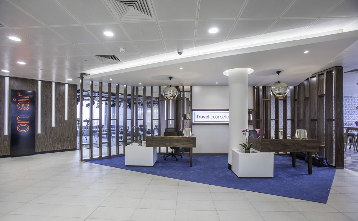 Open plan office reception with wooden desks and paneling
