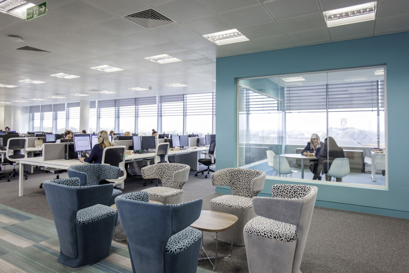 Open plan office design with staff working and a glass meeting room
