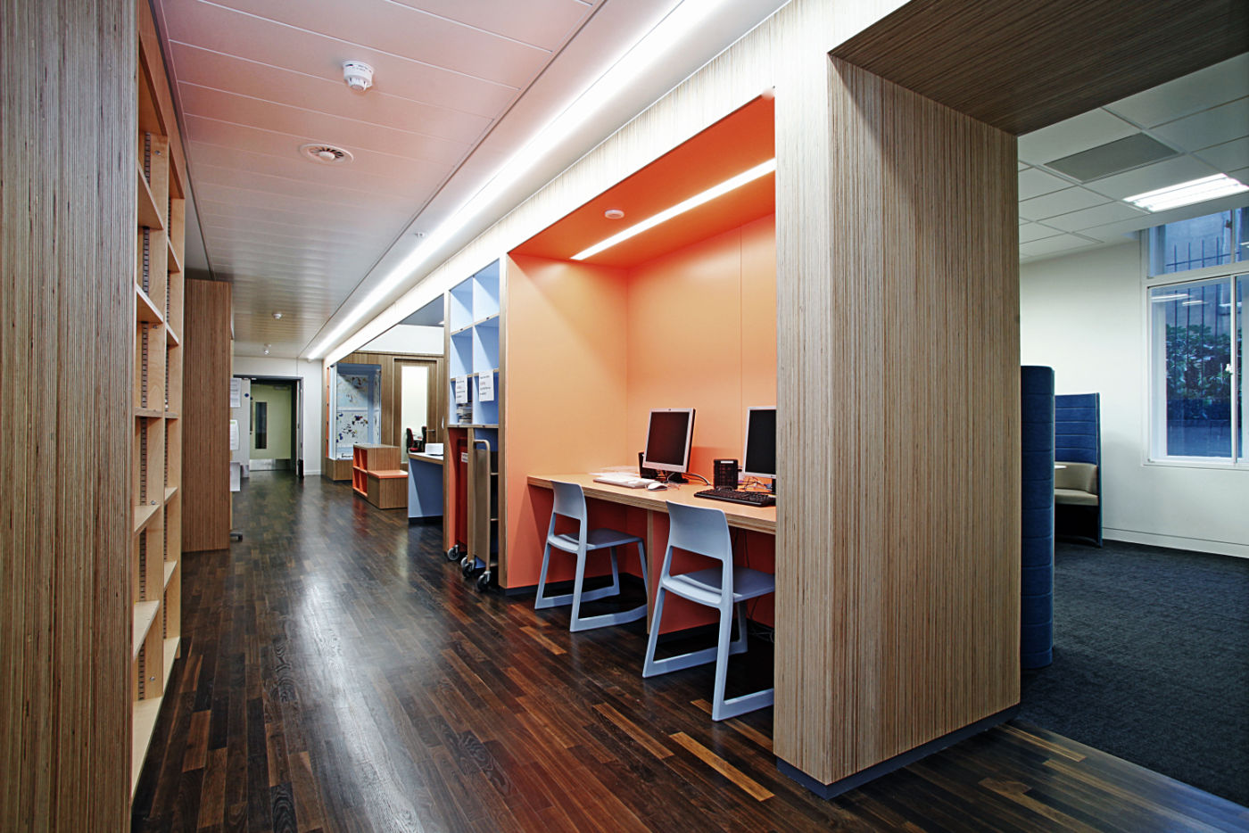 Computer stations in bright orange fit out